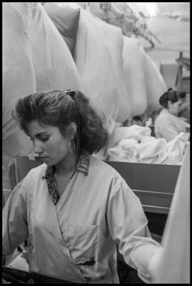 A laundry worker sorts tablecloths from huge laundry bags at California Linen Service