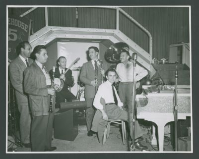 "Turk Murphy Jazz Band with Joe Darensbourg: Bob Helm, Joe Darensbourg, Dick Lammi, Turk Murphy, Wally Rose, Don Kinch, Bob Short (obscured).  Note the ""fire"" paraphernalia in the background.  This was likely a dual concert by Turk Murphy's Jazz Band and the Firehouse Five Plus Two; possibly at the Italian Village in San Francisco"