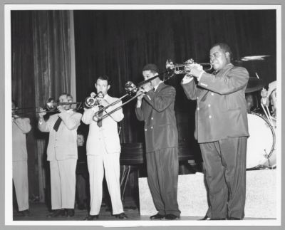 """""""Gene Norman Presents Just Jazz,"""" Pasadena Civic Auditorium, June 24, 1953. Members of Bob Scobey's Frisco Jazz Band and Louis Armstrong's All Stars. L to R: George Probert, soprano sax (partially obscured); Jack Buck, trombone; Marty Napoleon, piano; Bob Scobey, trumpet; Trummy Young, trombone; Louis Armstrong, trumpet; drummer (obscured)"""