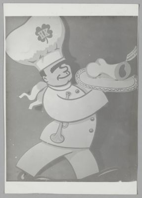 Photograph from Hambone Kelly's cartoon of Lu Watters in chef's garb with trumpet under arm and a plated hambone