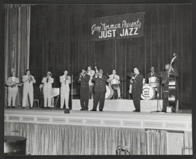 """Bob Scobey's Frisco Jazz Band on stage with Louis Armstrong and His All Stars at """"Gene Norman Presents Just Jazz,"""" Pasadena Civic Auditorium, June 24, 1953. L - R: Clancy Hayes, banjo; George Probert, reeds; Marty Napoleon, piano; Jack Buck, trombone; Bob Scobey, trumpet; Trummy Young, trombone; Squire Girsback, bass; Louis Armstrong, trumpet; Fred Higuera, drums; Barney Bigard, clarinet; Cozy Cole, drums; Arvell Shaw, bass"""