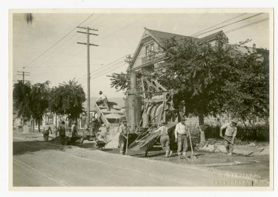 """Paving Telegraph Ave. in front of """"The Jaws,"""" note sections in truck, dumps one section at a time right into the hopper of the mixer"""